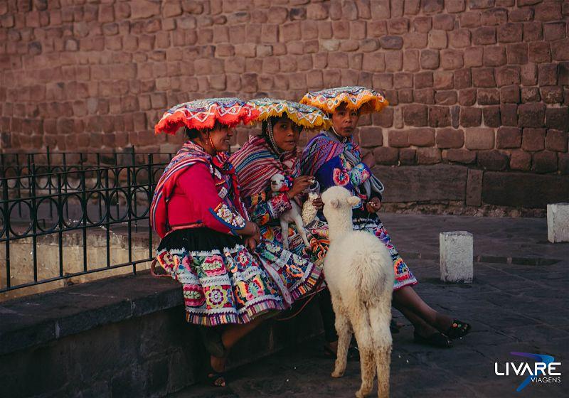 tres mulheres sentadas com trajes peruanos alimentando lhama