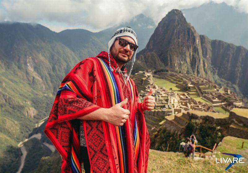turista com roupa tradicional peruana em frente a machu picchu