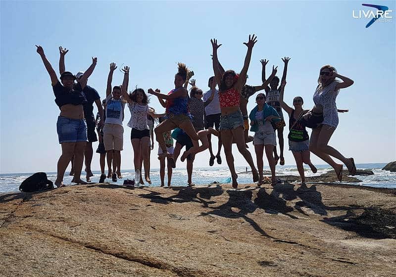 grupo de viajantes pulando felizes sobre pedra na excursao ilha do mel PR