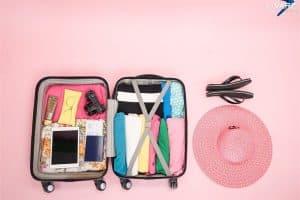 mala de viagem aberta com vários itens fundo rosa