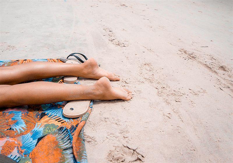 pernas de pessoa deitada sobre canga na areia da praia