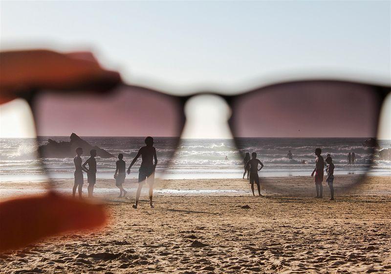 pessoa segurando oculos de sol com pessoas ao fundo caminhando na praia