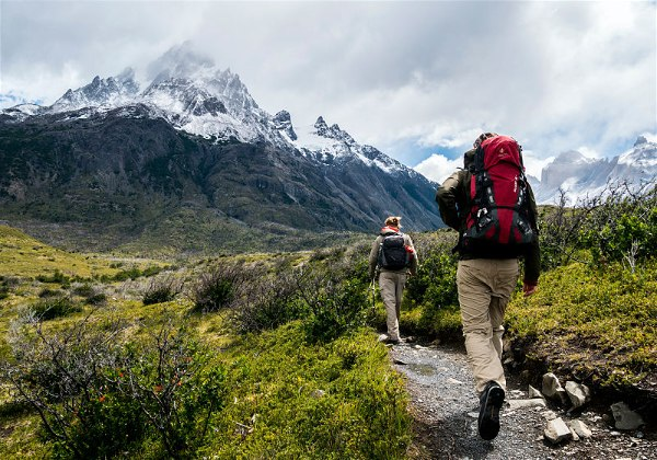 casal subindo montanha na argentina com mochila de camping nas costas