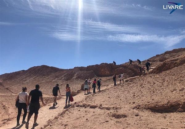 pessoas subindo montanha no deserto do Atacama em dia ensolarado
