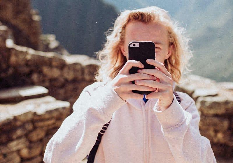 mulher com celular ao rosto tirando foto em machu pichu