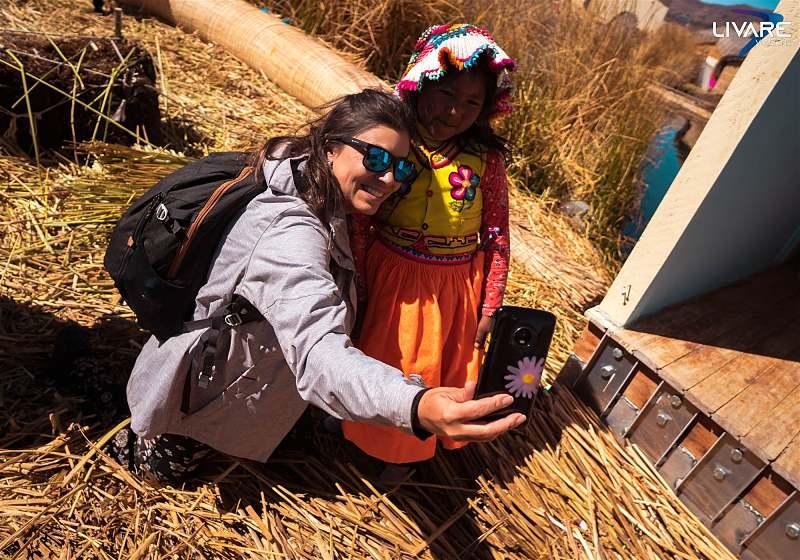 mulher sorrindo tirando selfie com menina indígena