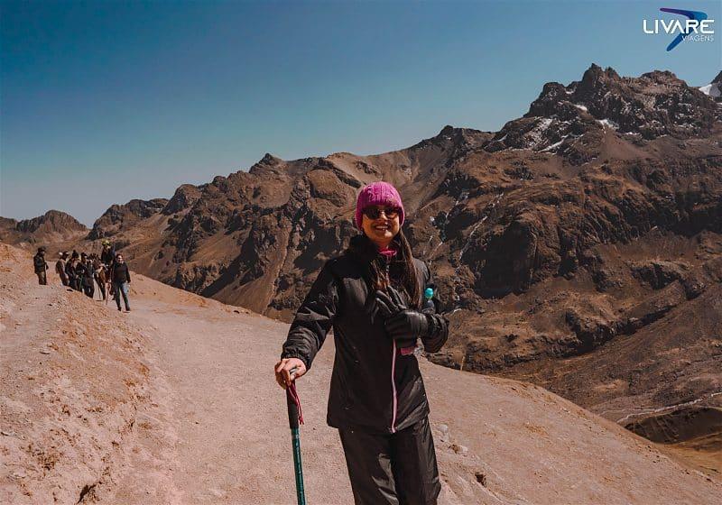 mulher com bastão na mão no trekking da montanha do arco-íris