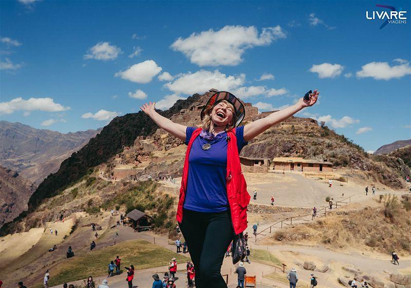 mulher de braços abertos feliz no valle sagrado dos incas