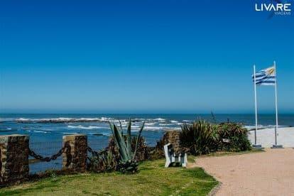 paisagem com banco e bandeira do uruguai com mar ao fundo