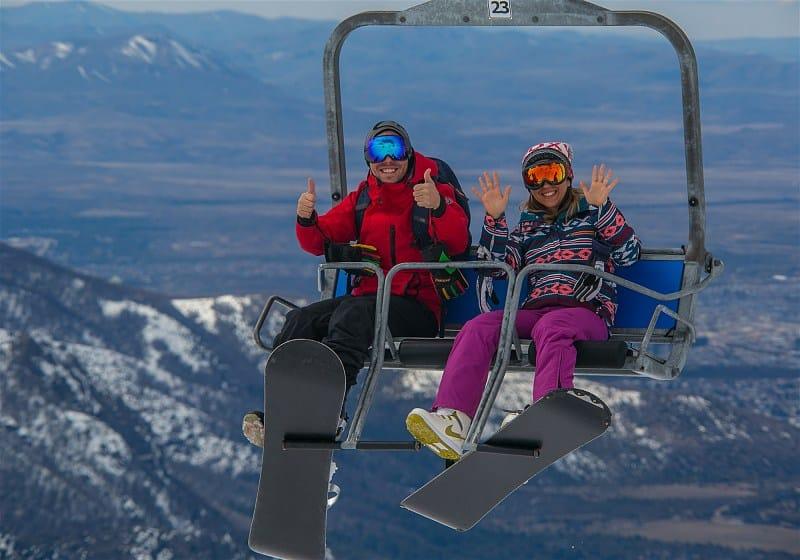 casal sorrindo e acenando em teleférico com montanhas nevadas ao fundo
