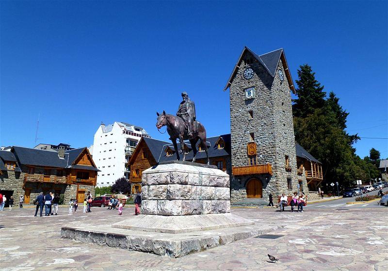 monumento julio roca no centro histórico de bariloche com contruções históricas ao fundo