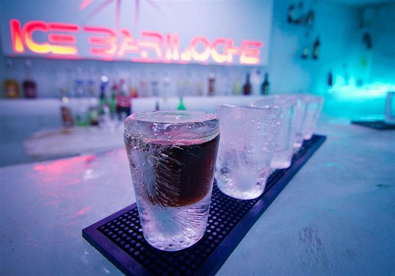 copos feitos de gelo no balcão letreiro do icebar ao fundo
