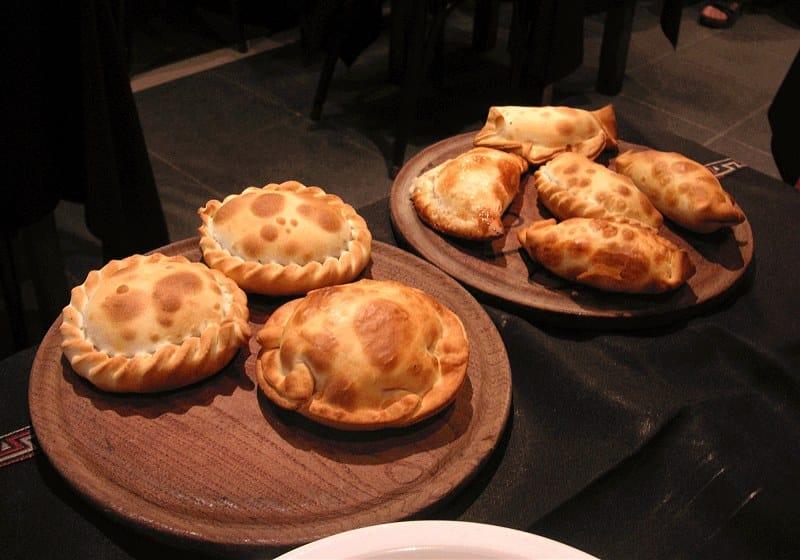 dois pratos de madeira com empanadas argentina