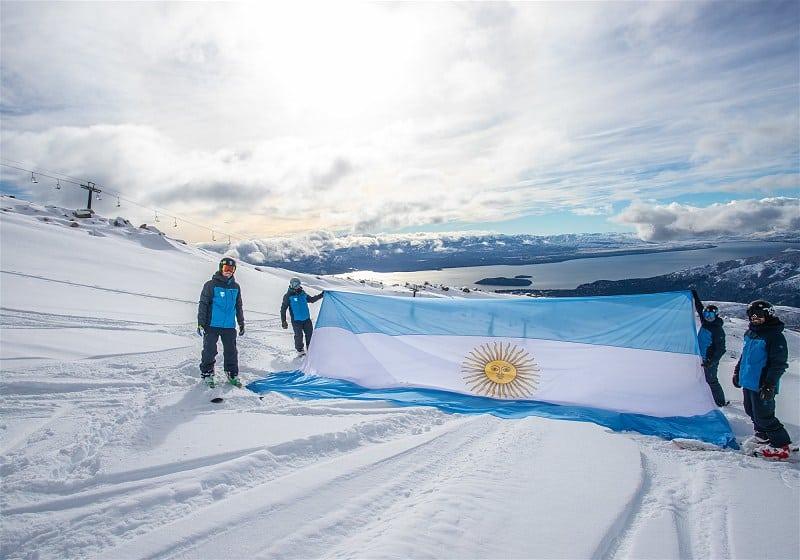 quatro homens segurando bandeira da argentina no topo da montanha com neve