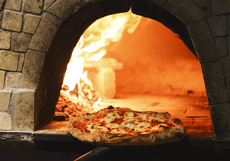 pizza sendo colocada no forno de barro