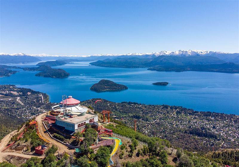 vista aerea de confeiteria giratoria no topo da montanha ao fundo cidade de san carlos bariloche com lago e montanhas nevadas