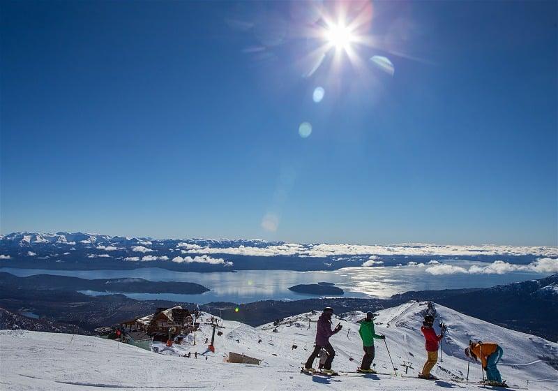 quatro pessoas esquiando no topo da montanha com vista ao lago nahuel huapi
