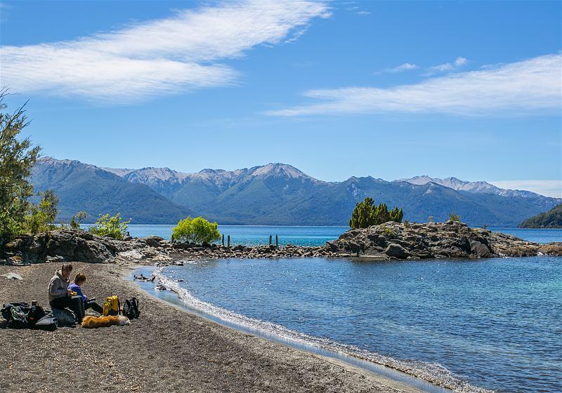 casal sentado na praia montanhas ao fundo em ilhas victoria em bariloche