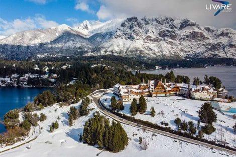 hotel llao llao com montanhas nevadas ao fundo e cercado por lagos