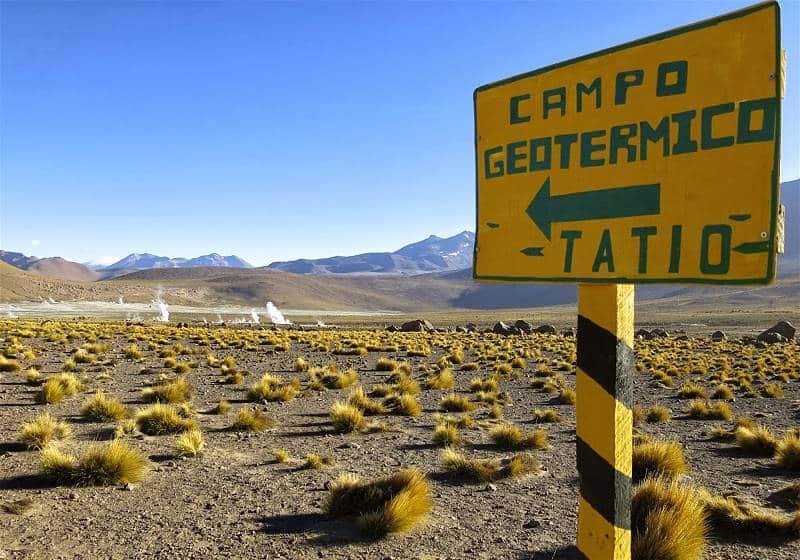 placa amarela indicando campo geotermico del tatio ao fundo fumarolas de vapor e cadeia de montanhas