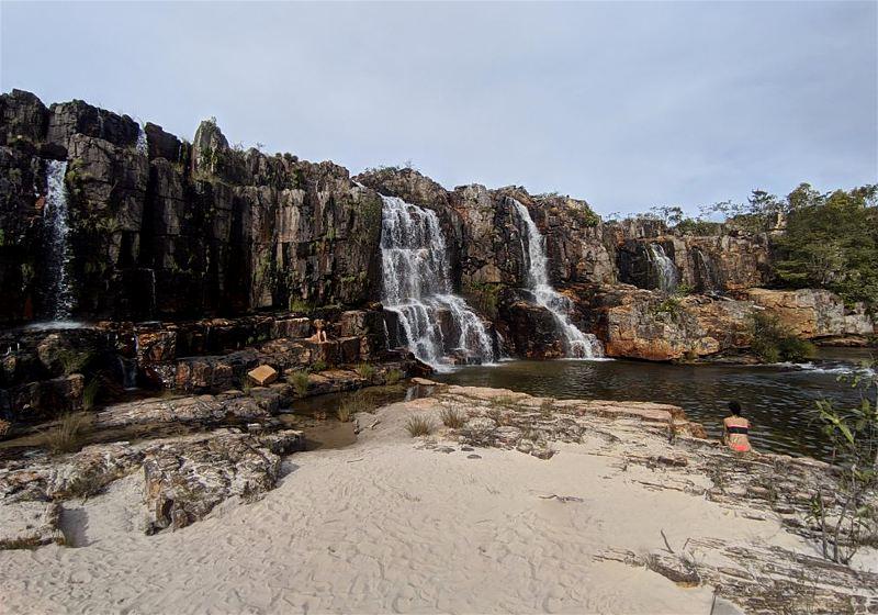 mulher sentada na faixa de areia contemplando a cachoeira da muralha