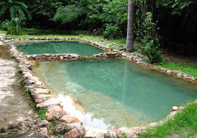 duas piscinas de águas termais cercadas por pedras e água cristalina