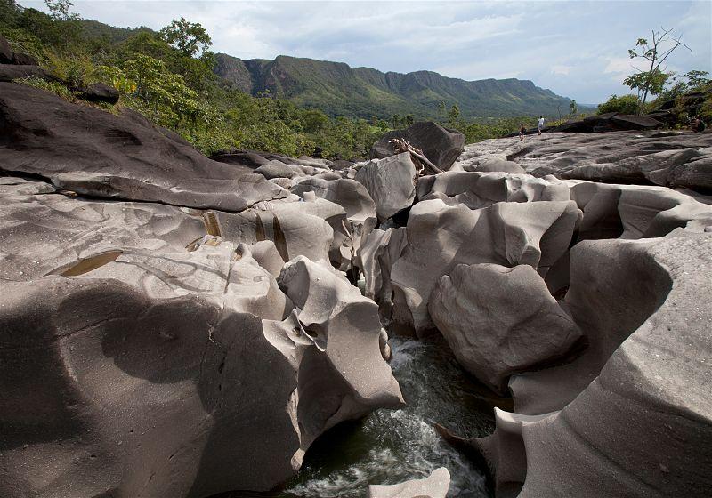 cadeia de rochas com formas similares a lua com filete de água passando entre e montanha ao fundo