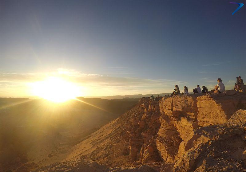 pessoas assistindo o por do sol na piedra del coyote deserto atacama