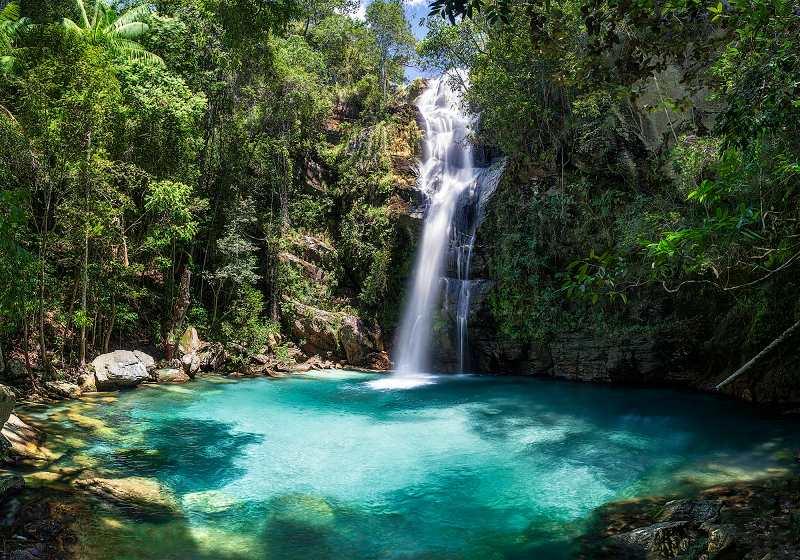 cachoeira em meio a mata fechada e água azul cristalina