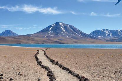 caminho de pedras em meio ao deserto com vulcão e montanhas ao fundo