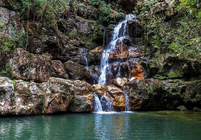 cachoeira loquinhas com água coloração esverdeada e vegetação