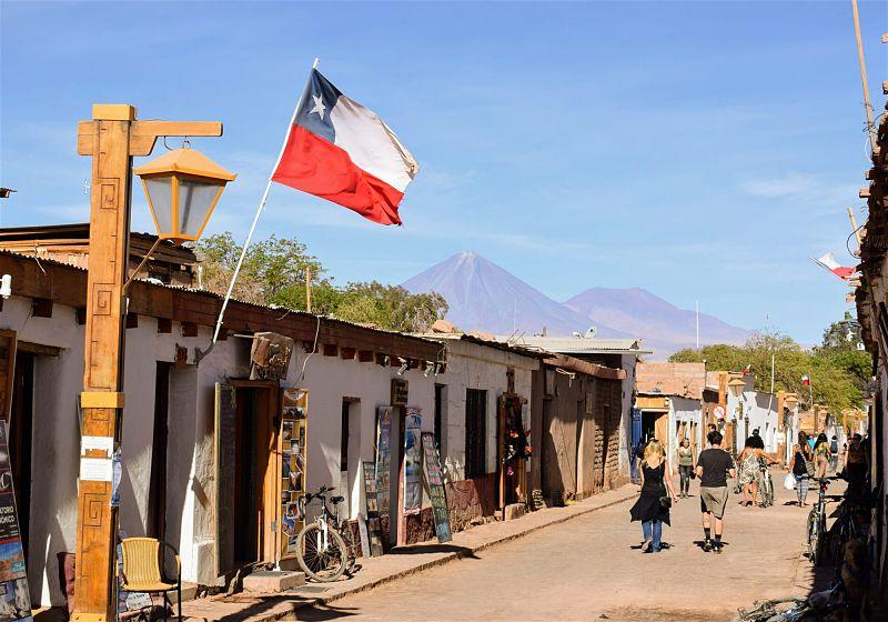 turistas passeando em rua em san pedro atacama com bandeira do chile e vulcões ao fundo